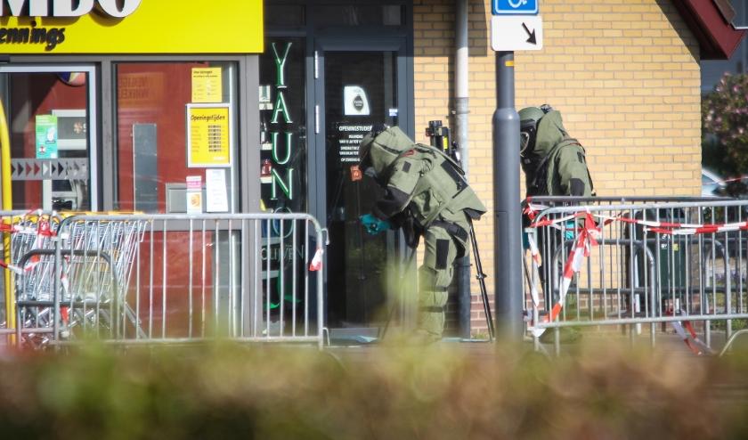 De EOD doet onderzoek bij de geldautomaat. Onder: een bewoner wordt geëvacueerd.