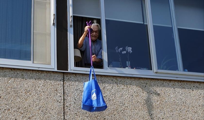 Bert Slok, bewoner van 't Boveneind, hijst zijn boodschappen naar boven. Dochter Ieke heeft daar voor gezorgd. (Foto: PR)