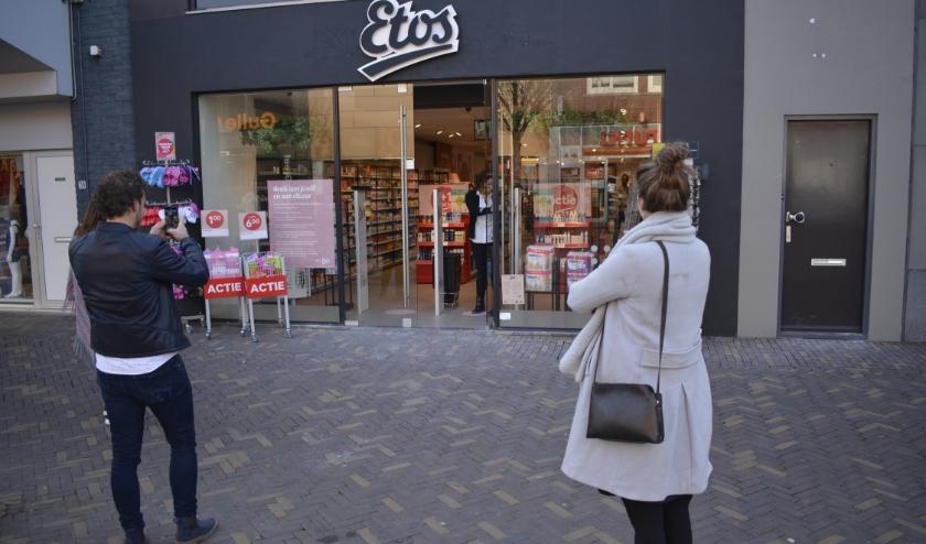 De winkel gaat open. Vrienden Bart en Daniëlle uit Elst zijn de eerste klanten. Bart maakt zelfs foto's. (Foto's: Pieter Vane)