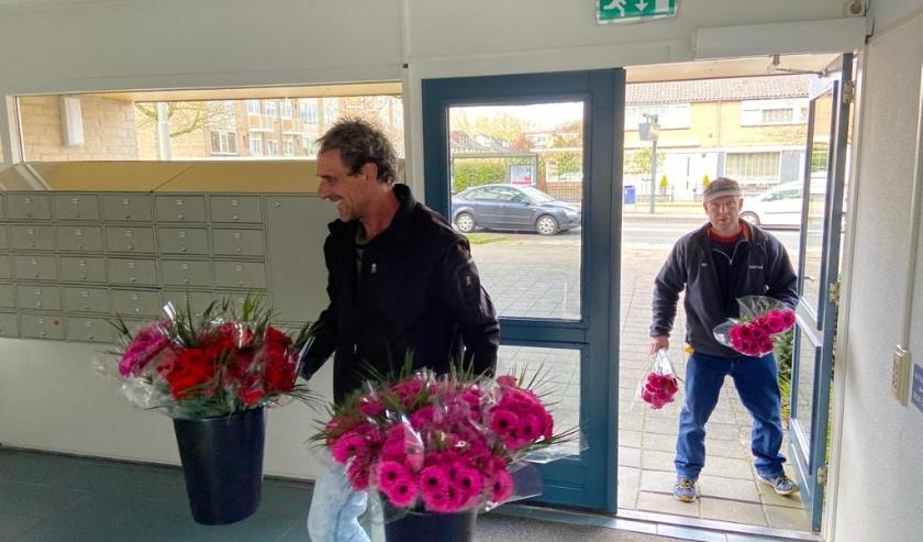 Medewerkers van Portaal plaatsen bloemen in de centrale hal van een van de zeven woongebouwen.