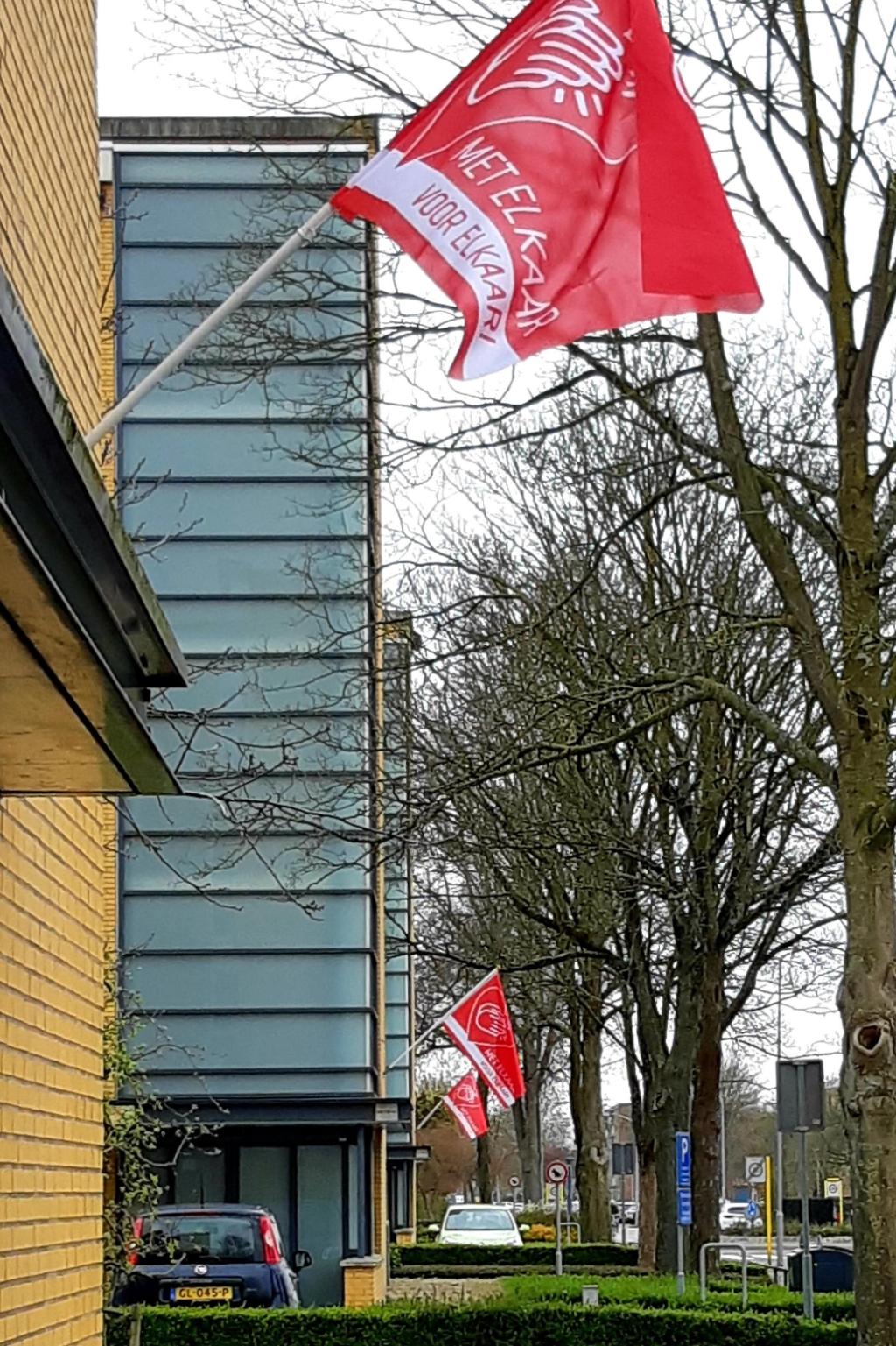 In rood-witte kleuren wapperen aan de Wadenoijenlaan – ter hoogte van het winkelcentrum Kwadrant – de vlaggen die verbondenheid etaleren. Foto: Marianne van der Ven © DPG Media