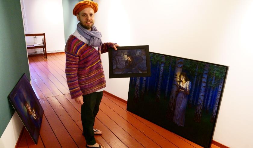 De Zwolse kunstenaar Daniel Douglas met enkele van zijn werken in het Voerman Museum Hattem. (foto: Voerman Museum Hattem)