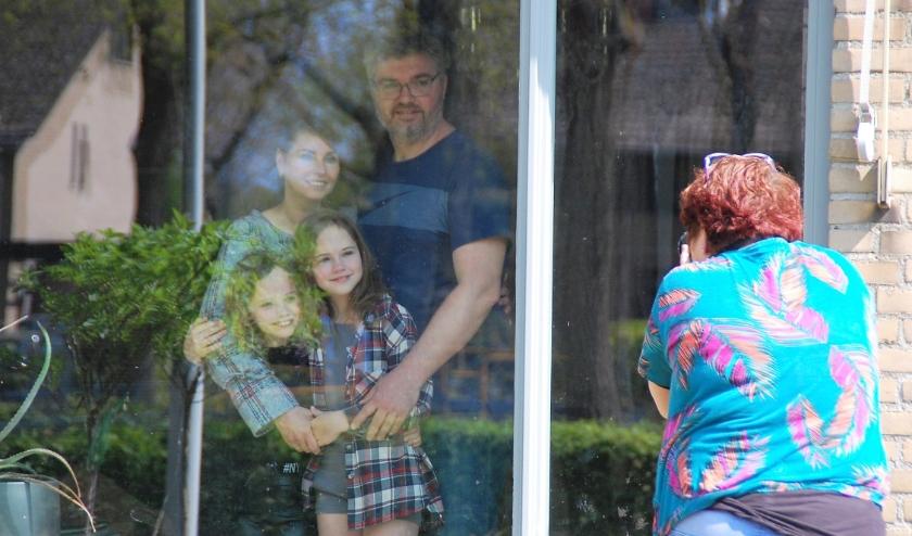 De familie Yvonne, Corné, Luna en Ariëlle Peijs uit Middelbeers laat zich gewillig achter hun raam fotograferen. De verjaardag van Corné voelt anders dan anders.