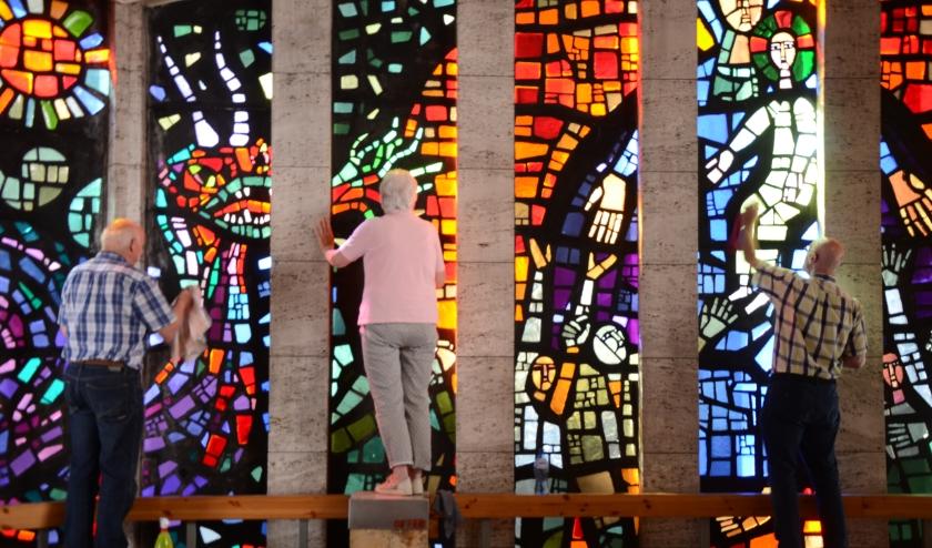 Vrijwilligers zijn bezig om de glazen te poetsen, zodat de Kapel OLV Ter Nood er mooi bij staat tijdens Dodenherdenking en Bevrijdingsdag. Foto: Paul Spapens.