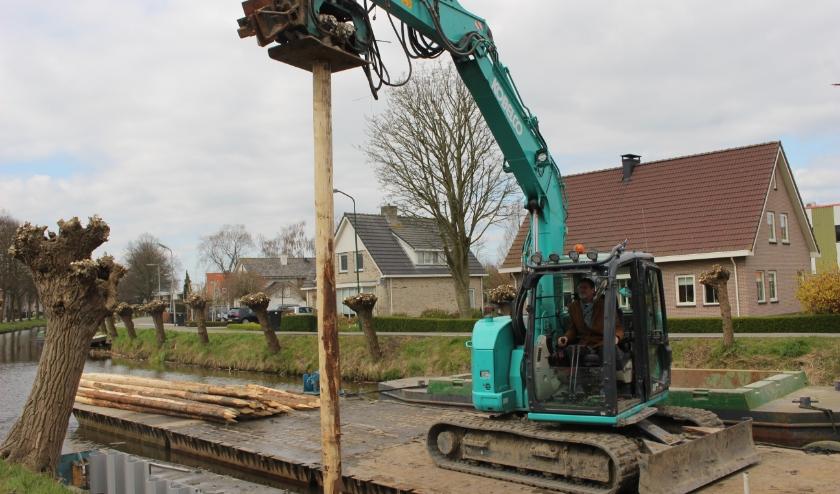Om de oevers te stabiliseren wordt nu een kunststof beschoeiing met houten afwerkrand geplaatst. Wethouder Bob Duindam sloeg de eerste paal. (Foto: gemeente Oudewater)