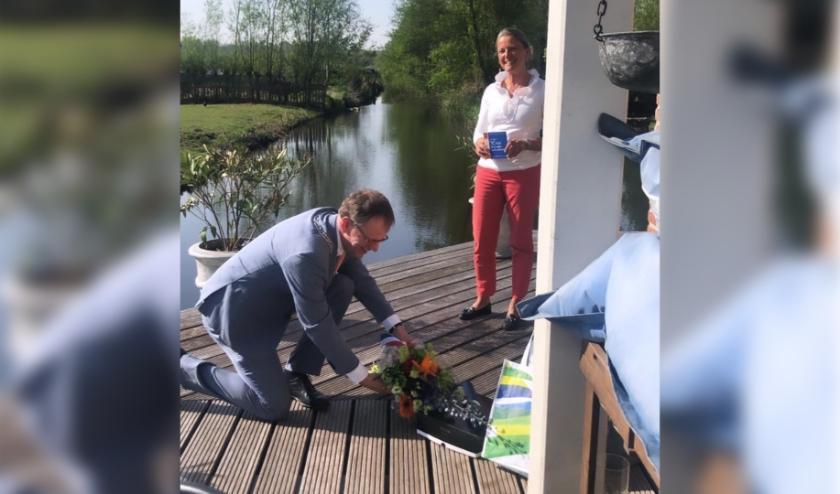 Burgemeester Christiaan van der Kamp gaat letterlijk door de knieèn voor Angenieta Kaatee-de Groot. Foto: Christa Abels