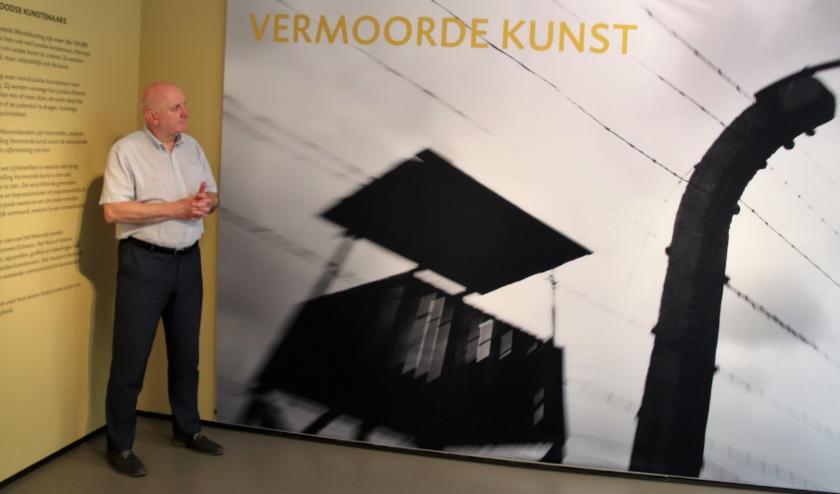 Erik Stotijn bij de foto van Auschwitz als introfoto bij de expositie Vermoorde Kunst.