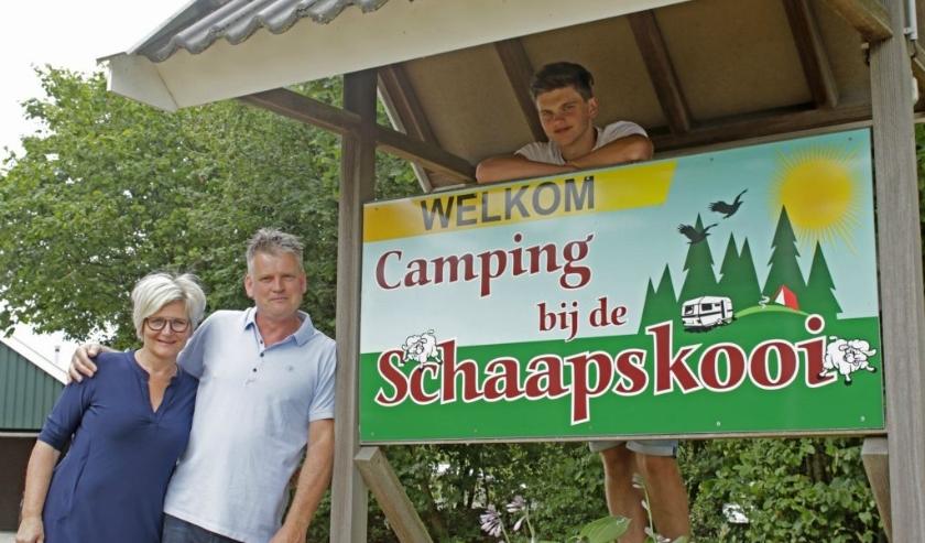 Monique en Anton Vrielink bij de ingang van camping De Schaapskooi. Achter het bord zoon Jordi.