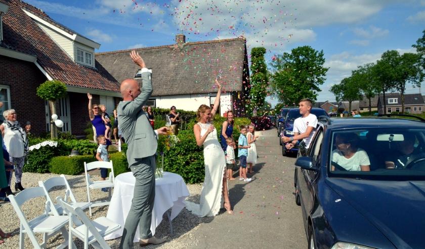 De inzittenden van een lange stoet auto's feliciteerden het kersverse bruidspaar Wim Vendrig en Kitty Vendrig-Koorenvaar hun kinderen en familieleden. (Foto: Paul van den Dungen)
