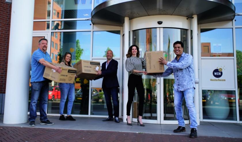 Menno, Diana en Tico doneren de mondkapjes aan Wendy en Marco van Woonzorgcentra Haaglanden. Foto: Robbert Roos