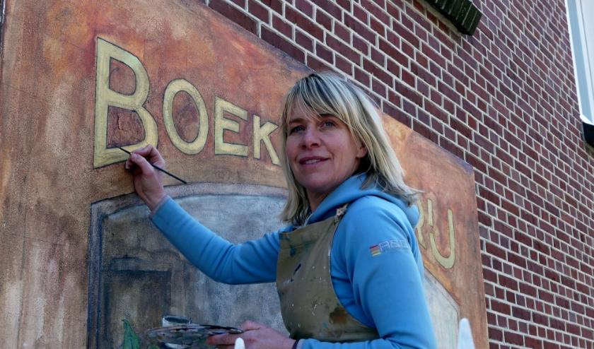Femmie den Ouden bezig aan een muurschildering in Silvolde.