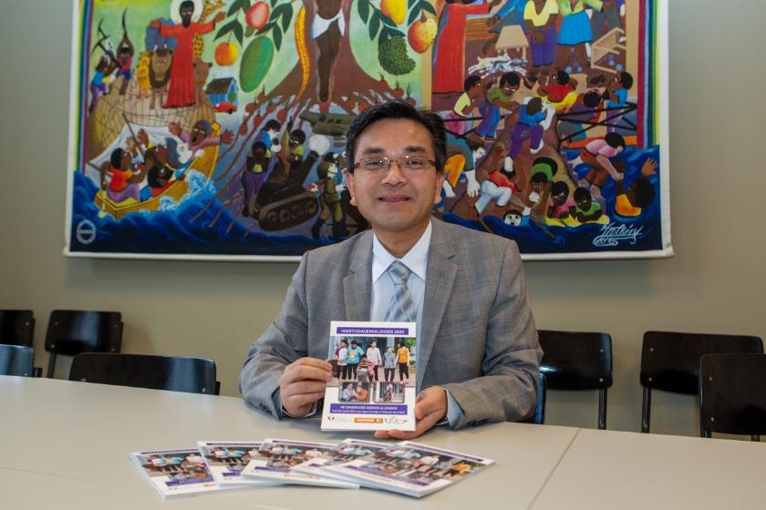Pastoor Thanh Ta toont de vastenkalender met informatie over het project voor gehandicapten in Vietnam.