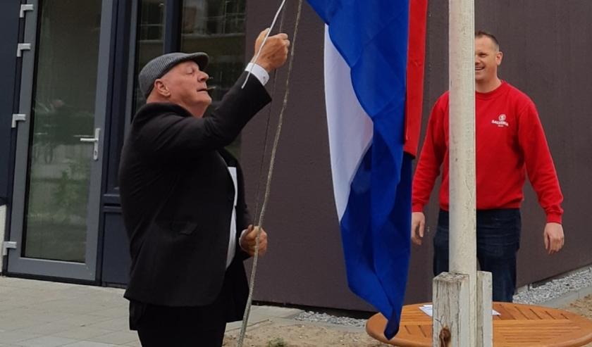 De vlag wordt gehesen door meneer Smeets, bewoner van één van de vernieuwde appartementen.