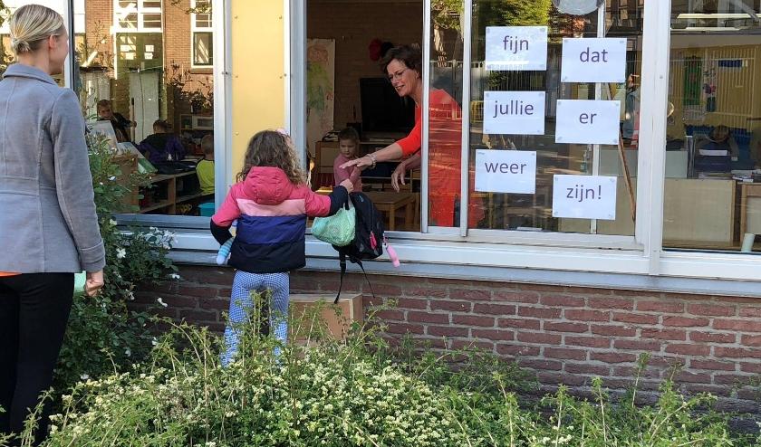 Juf Anja Gort helpt een van haar kleuters om via het 'trappetje van Van Hameren' en het raam de klas binnen te komen.
