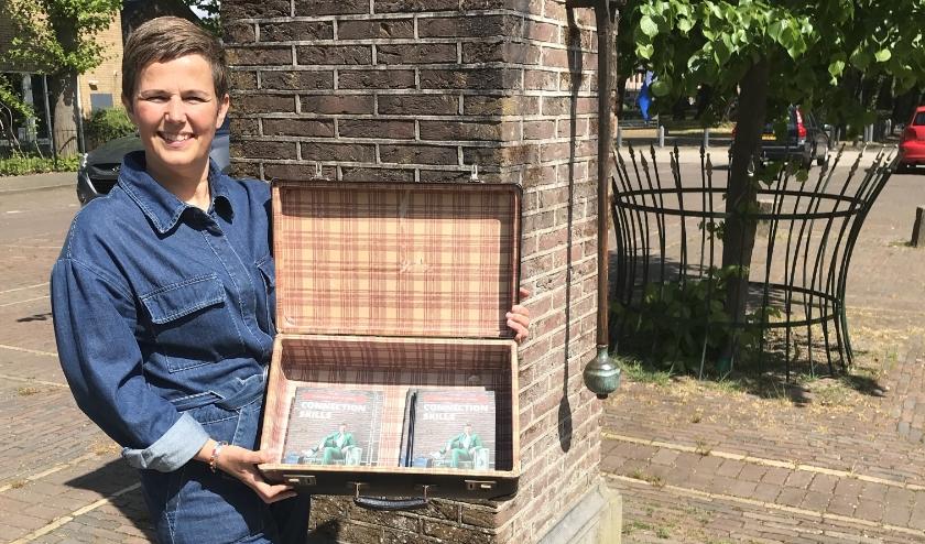 Bij de oude pomp op het Dorpsplein toont Linda Commandeur vol trots haar boek 'Connection Skills'.
