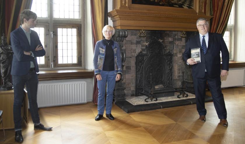 Anneke Nolet biedt haar boek 'Vrouwen in Verzet' aan aan  burgemeester Hubert Bruls. Links historicus Lennert Savenije.