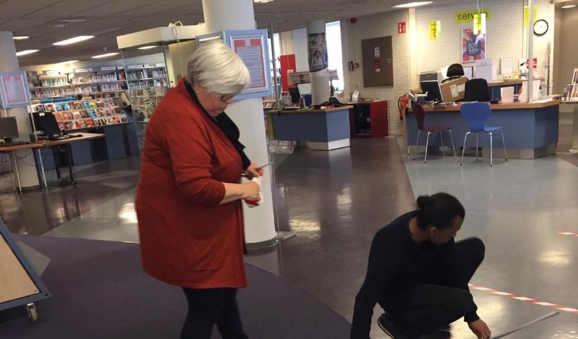 Medewerkers Lilian en Roar van de bieb bezig met het aanbrengen van plakstrips om de anderhalve meter afstand duidelijk te maken.