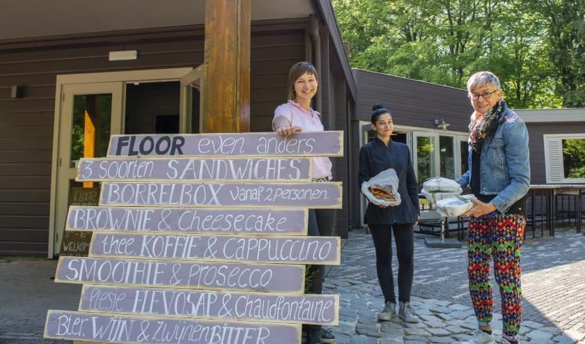 Medewerkers Marjolein Tuinman (links) en Veronica Cadoni overhandigen ovengerechten aan één van de vele Epenaren (rechts) die gebruikmaakten van 'Floor Even Anders'. Foto: Dennis Dekker