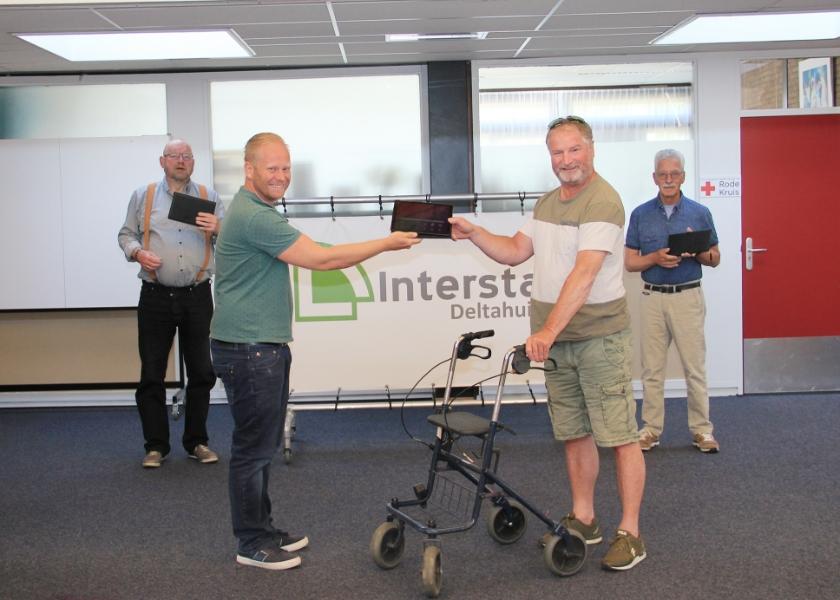 Niels Schoterman van Interstap overhandigt een tablet aan Johan Corbijn. Achter Harry van den Berg (l) en Ben Seeger.
