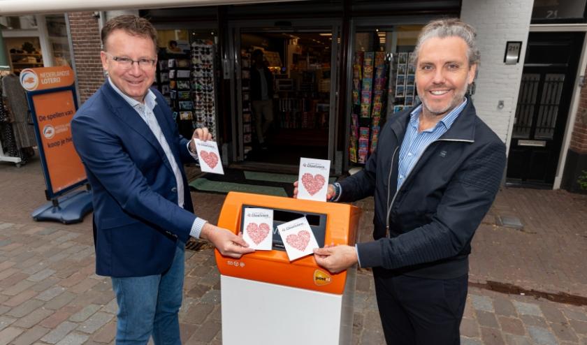 Burgemeester Patrick van Domburg en initiatiefnemer Martin Planken met de wenskaart (Foto: Edward van Osendarp)