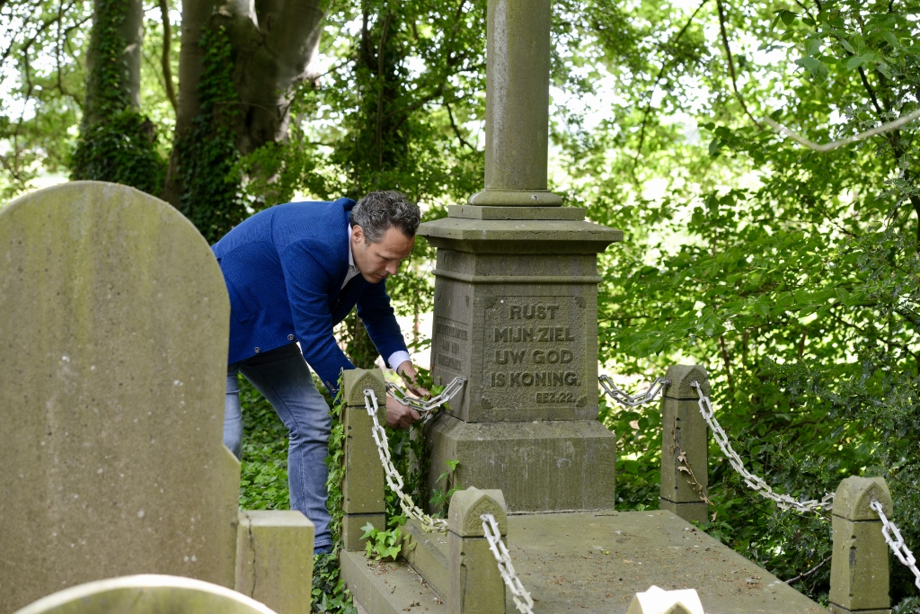 wethouder Rutger van Stappershoef haalt klimop weg om tekst op steen van vermoorde burgemeester te kunnen lezen. Foto:                                      © DPG Media