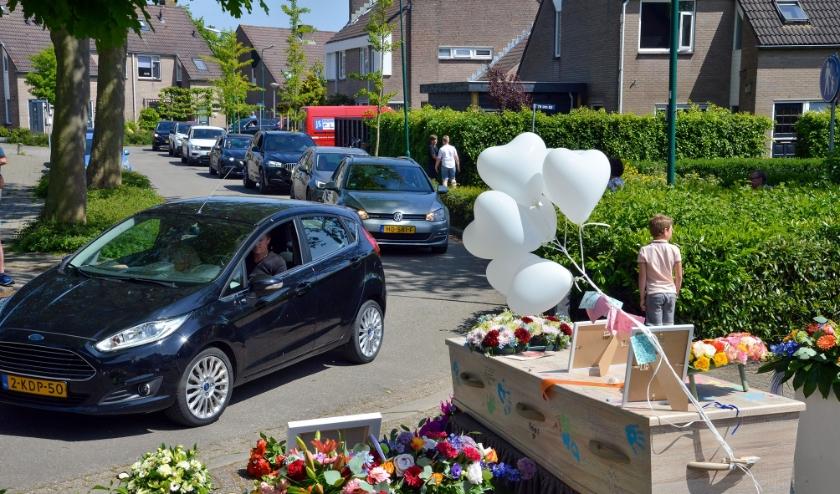 Met het passeren van de voor zijn woning opgestelde kist en het leggen van bloemen brachten tal van mensen een laatste groet aan de onlangs overleden Jan van der Stoep. (Foto: Paul van den Dungen)