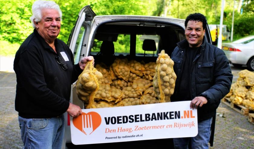 Klaas Spikman (l) van Voedselbank Zoetermeer neemt de aardappelen van Tico Roozendal graag in ontvangst. Foto: Robbert Roos