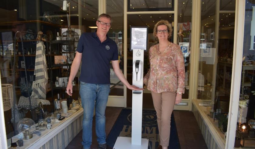 Henri en Everdien bij de hygiënezuil voor hun winkel. (Foto: Jolien van Gaalen / Van Gaalen Media)