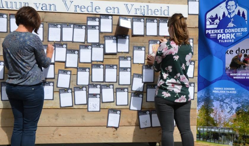 Bezoekers van de tentoonstelling worden gevraagd een boodschap achter te laten op de 'Muur van Vrijheid en Vrede'.