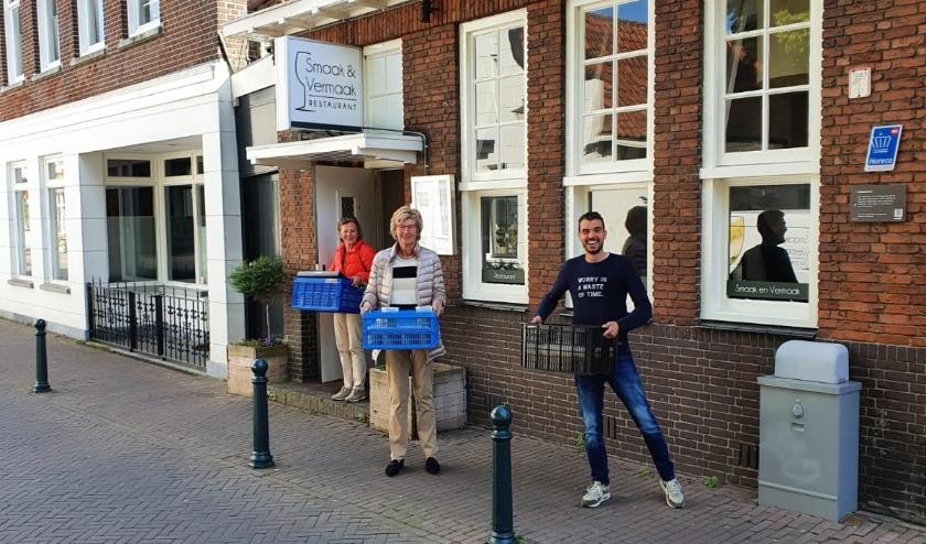 Op de foto verlaten bestuursleden Marjolijn Klopper en Dini Bouwmeester (van links naar rechts) het restaurant Smaak & Vermaak met kratten soep, die ze bij de leden van TV Seghwaert gaan bezorgen. Eigenaar en chef Sander Beentjes helpt erbij