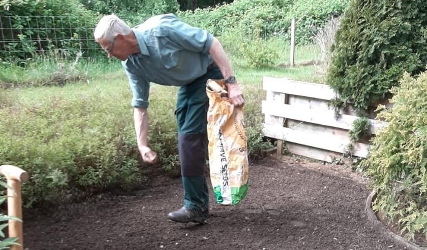 Een vrijwilliger van Present zaait het gras in.