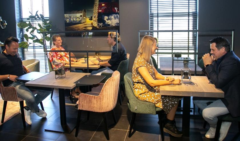 Links een tafeltje met 'spacers' en tussen de tafels staan de spatschermen. (Foto: Jeroen Verbueken)