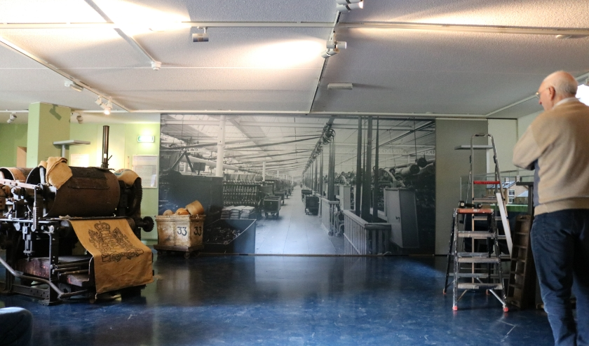 RIJSSEN - Gerrit Kreijkes van de Technische Dienst van het museum bekijkt het zojuist opgehangen doek van de juteweverij in de kelder van het Tweede Bouwhuis. (Foto: Jan Joost)