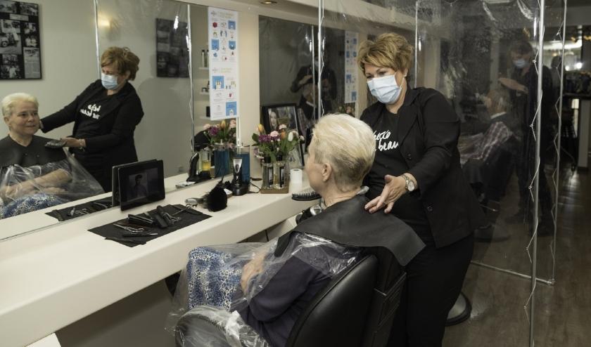 Claudia kan eindelijk weer doen waar ze goed in is: de klanten van haar kapsalon blij maken. (Foto Jan van den Berg)