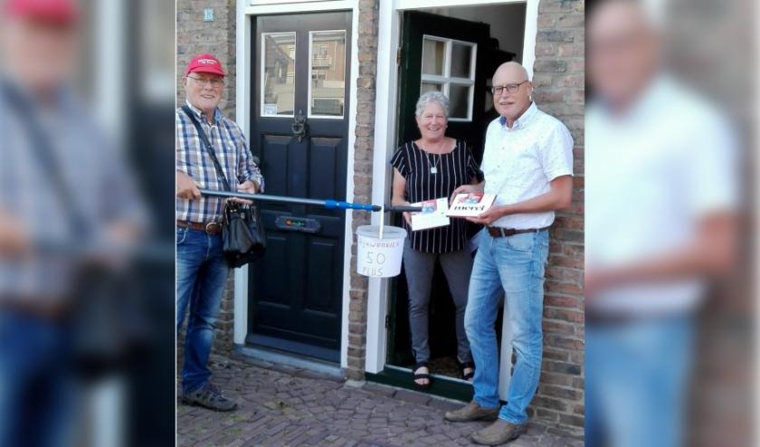 Eef Rieswijk bij de familie Spanbroek - op anderhalve meter - om de verrassing af te leveren. (foto: John Stoll)