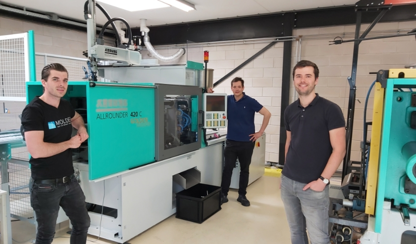 Jeroen Compen, Martijn van de Ven en Jeroen Raijmakers naast de twee spuitgietmachines waaruit dagelijks 30.000 kunststof teststaafjes rollen.