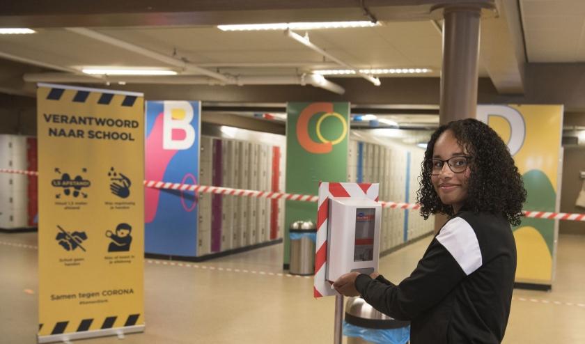 Thomas a Kempis in Arnhem is helemaal klaar voor de heropening van het voortgezet onderwijs. Isabelle Hakvoort demonstreert de automaat met handgel.  (foto: Ellen Koelewijn)