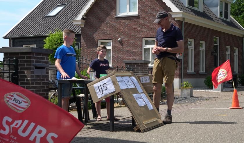 De 12-jarige Lars van Rangelrooij biedt wandelaars en fietsers ijs- en ijskoud drinken aan. Hij krijgt hulp van zijn buurjongentje Teun Broere.