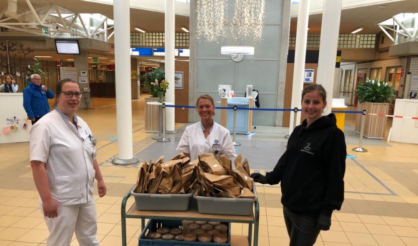 Medewerkers van het UMC nemen de lunches van restaurant de Witte Zwaan dankbaar in ontvangst.