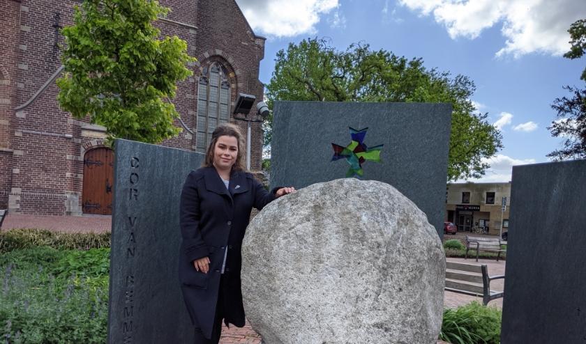 Sanne Telgenkamp van Stadsmuseum Woerden bij het oorlogsmonument Cor van Bemmel, dat bestaat uit vier zuilen die rondom het 4 mei beeld 'de kei' staan.
