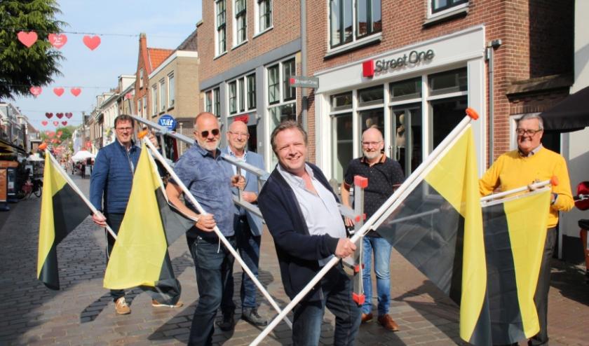 Alle leden van het Comité IJsselstein 700 jaar Stad zorgden er - met ondernemer Frits Mulder - voor, dat de IJsselsteinse vlaggen ook in de winkelstraten hangen. (Foto: Lysette Verwegen)