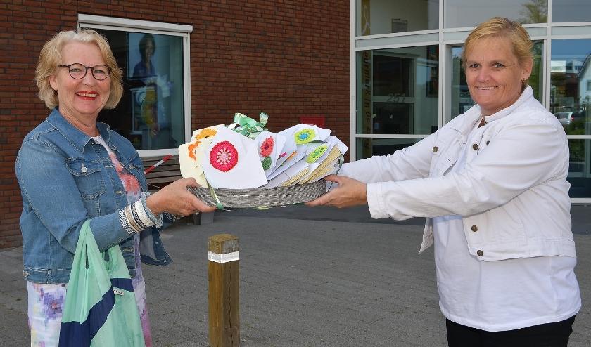 Jannie (links) overhandigd de kaarten aan Desiree Voskamp van De Vijverhof. (Foto: Jan van der Arend)