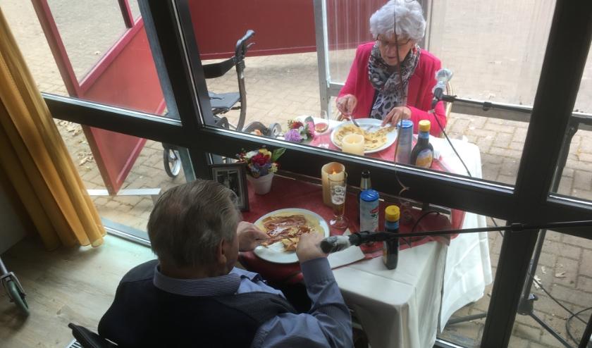 Mensen dineren met glasraam ertussen, 1 binnen en 1 buiten.