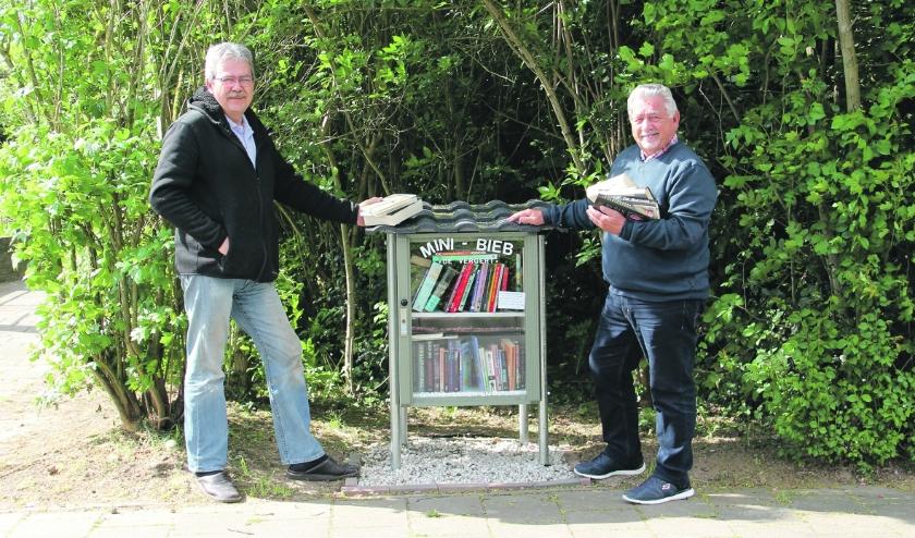 Wim Möller (rechts) en Jan Eijkelboom bij de nieuwe minibieb in de wijk De Vergert.