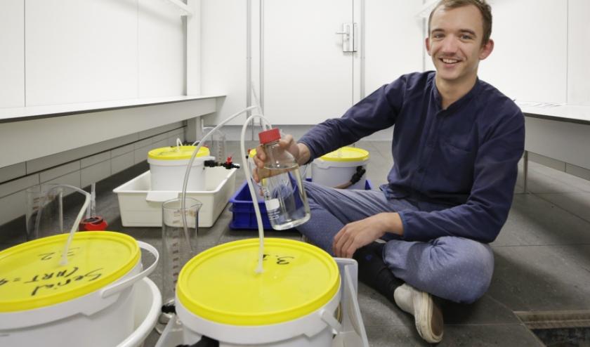 Vincent bij zijn provisorisch opgestelde installatie van gekoppelde biogasreactoren. Foto: Jurgen van Hoof