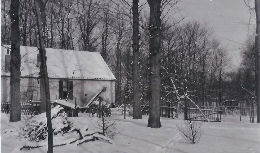 Een besneeuwde woning in een bos, maar waar?