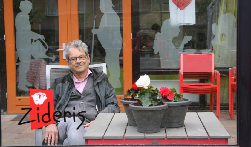 Begeleider Luc Herfs op het terras van de dagbesteding van Zideris bij de Koperwiek.  De glazen wand scheidt de bewoners van hun bezoek