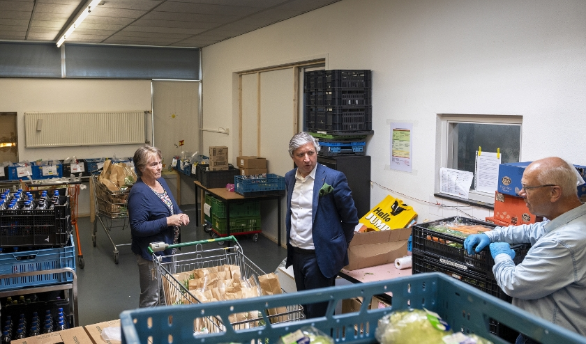 Joke Steigerwald van Voedselbank Rivierenland Tiel leidt burgemeester Hans Beenakker rond.