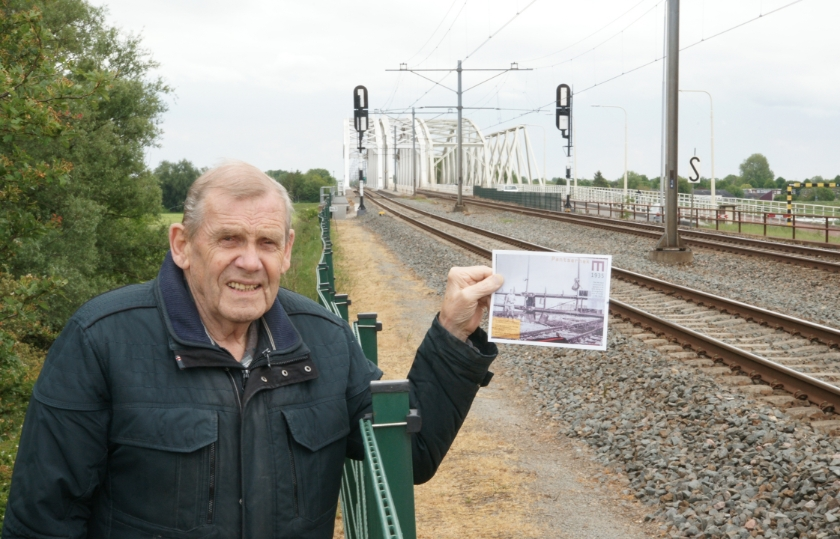 Bennie Weijers bij de spoorlijn. In zijn hand heeft hij een foto van het pantserhek dat in 1940 op deze plek over de spoorbaan werd gezet.