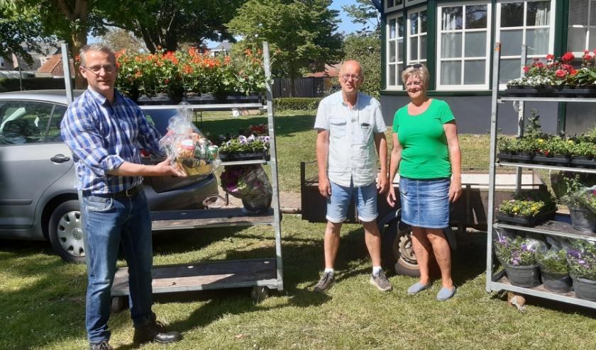 De voorzitter Jeroen Tijhuis overhandigt het cadeau aan de bloemenkoning Jan Dijsselhof en zijn vrouw Rineke.